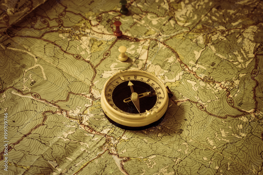 Fototapety, obrazy: Retro compass is on top of the old tourist map with drawing pin. The arrow of the compass indicates the route of movement of tourists. The northern direction.