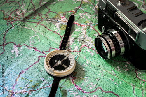 Photo  Retro photoapart and compass are on top of the tourist map