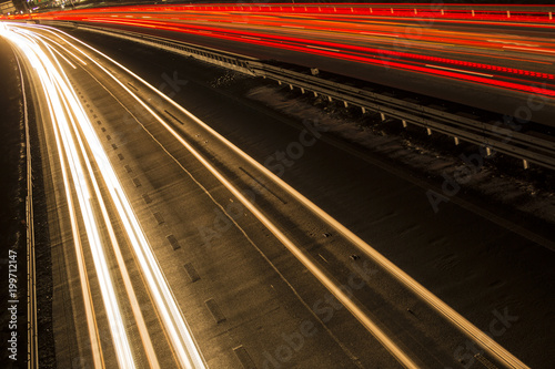 Foto op Aluminium Nacht snelweg Night scene of motion blurred light tracks glowing to the darkness of highway traffic to the city just after sunset. Creative long time exposure diagonal composed photography.