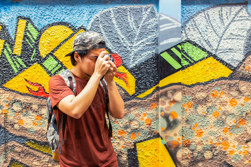 Young asian travel tourism using film camera vintage take a photo at street art in Bangkok.