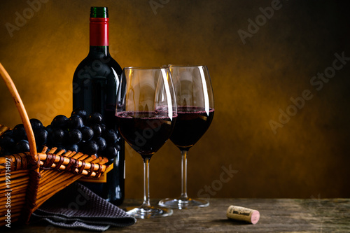 Fototapeta Still life with bottle of red wine, two wineglasses and grape in a wicker basket with copyspace for text obraz