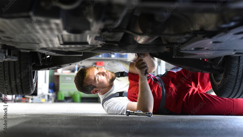 Fototapeta Automechaniker repariert Fahrzeug in einer Werkstatt in Arbeitskleidung am Unterboden - Closeup // Car mechanic repairs vehicle in a workshop in work clothes on the underbody