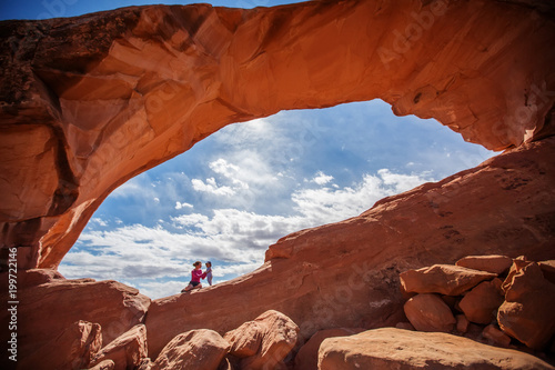 Mother with her baby son stay below Skyline arch in Arches National Park in Utah, USA
