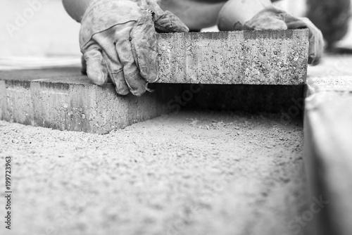 Fototapeta Greyscale image of workman laying a paving brick