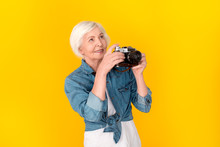 Senior Woman Traveler Studio Isolated On Yellow Wall Taking Photos On Camera