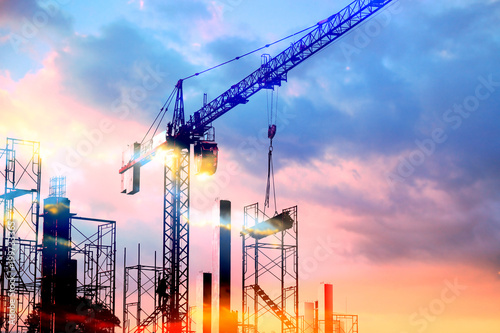 tower cranes at construction site with sun