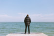A guy in a jacket by the sea looks at the horizon