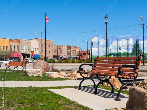 Cuadros en Lienzo  Park bench in small town USA main street with commercial storefronts