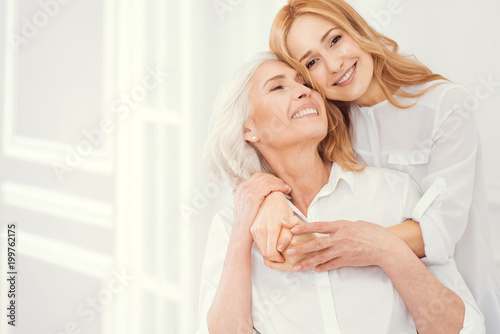 Fototapeta Forever thankful. Sweet moment of expressing love between retired mother and her loving daughter wearing matching attire at home. obraz