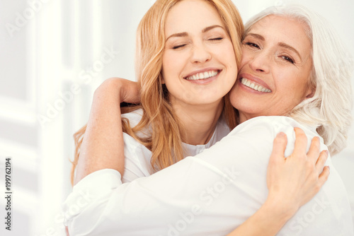 Fototapety, obrazy: Happiness is homemade. Sunshiny mature daughter and her elderly mom grinning broadly into the camera while embracing and enjoying a happy family moment spent together.