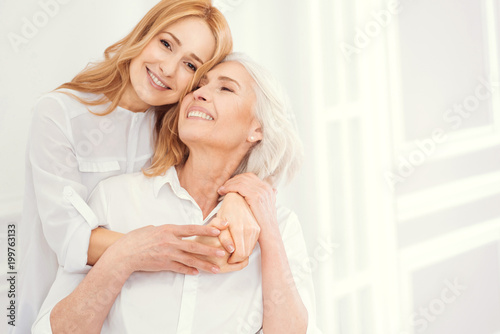 Fototapety, obrazy: Love you to the moon and back. Full of love charming blonde lady smiling into the camera while standing next to her beautiful mother and hugging her tightly to express her love.