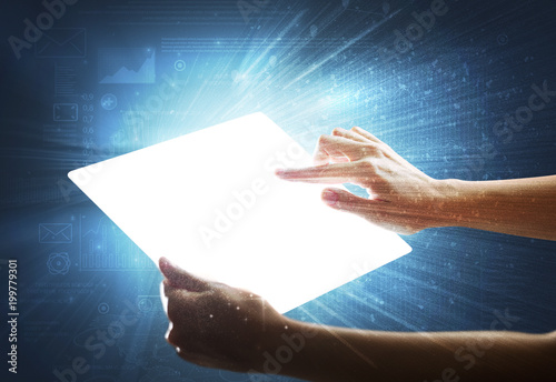 Fototapety, obrazy: Young female hand holding a tablet with faded charts in the background