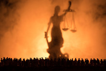 Silhouette Of Blurred Giant Lady Justice Statue With Sword And Scale Standing Behind Crowd At Night With Foggy Fire Background. At Night