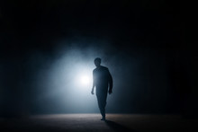 Dark Silhouette Of Slim Man Walking On The Street At Night. Being Alone. Lighted Street. Thief Sneaking In The Street.night Crime