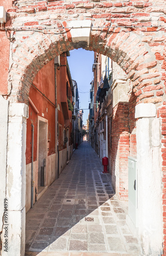 Foto op Canvas Smal steegje access to a narrow alley by a brick arched doorway. Venice, Italy