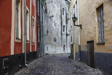 wąska brukowana uliczka między kamienicami na starym mieście