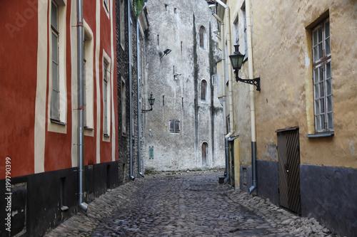 Fotobehang Smal steegje wąska brukowana uliczka między kamienicami na starym mieście