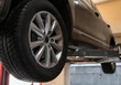 Car on hydraulic vehicle lift in garage, closeup. Tire service