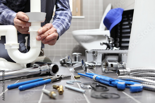 Fotografie, Tablou  plumber at work in a bathroom, plumbing repair service, assemble and install con