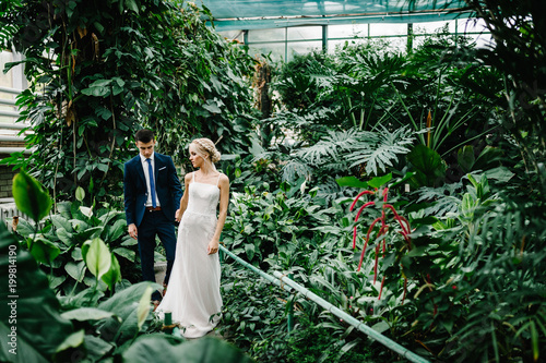 Portrait the groom in wedding suit and the bride in dress are going in the Botanical green garden full of greenery. Wedding ceremony. Newlyweds.