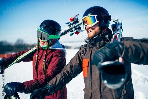 Poster Wintersporten Male and female skiers poses with skis and poles