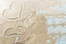 Inscription On A Sandy Beach On A Light Wooden Background.
