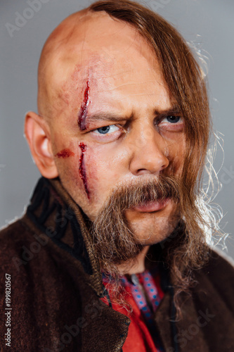 Photo  Severe warrior Russian Cossack, face in scars, bald