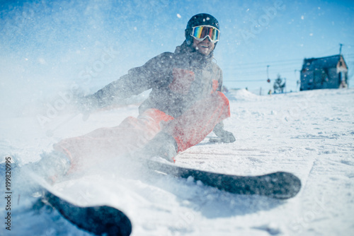 Tuinposter Wintersporten Skier lies on snowy surface of speed slope