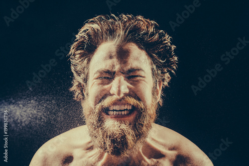 Valokuva  A bearded man angrily screams into a spray of water against a black background