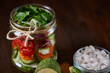 Delicious vegetable salad in jar and fresh veggies on cutting board on table, selective focus, close-up