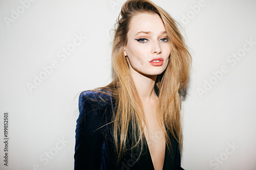 Portrait of prettygirl in blue velvet jacket standing and thoughtfully looking in camera on white background isolated