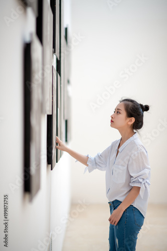 Fototapeta woman looking at the pictures on the wall obraz