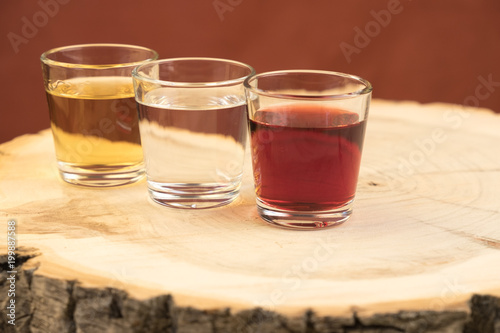 Poster de jardin Bar three glasses with different spirits are located on a wooden stump with annual rings, the texture of the cut is visible
