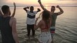 PAN of happy young people dancing in lake and partying at sunset on beach