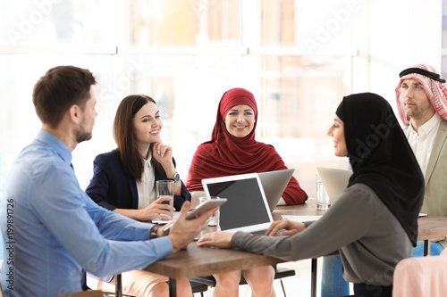 Office employees and their Muslim coworkers having business meeting in office