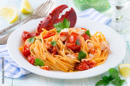 Spaghetti with lobster and cherry tomatoes served on white plate