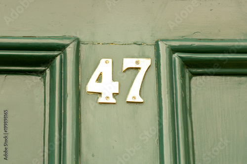 Fotografia  House number 47 sign on green painted door