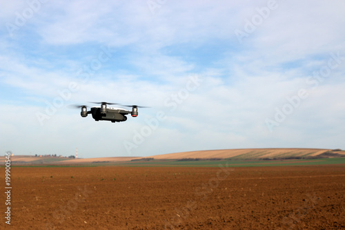 The drone is flying over the plowed field spring season