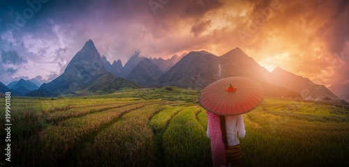 Fotobehang Rijstvelden Woman holding traditional red umbrella on rice fields terraced at sunset in Sapa, Vietnam.