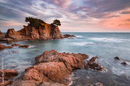 Scenic view of rocks in sea against cloudy sky