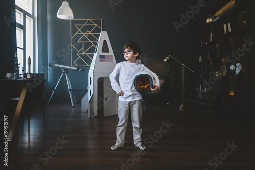 Cute little dreamer boy posing with a helmet at home, pretending to be an astrou Canvas Print