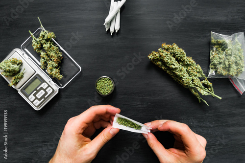 Fényképezés Not fully rolled jamb joint in the hands of a man marijuana weed The concept of
