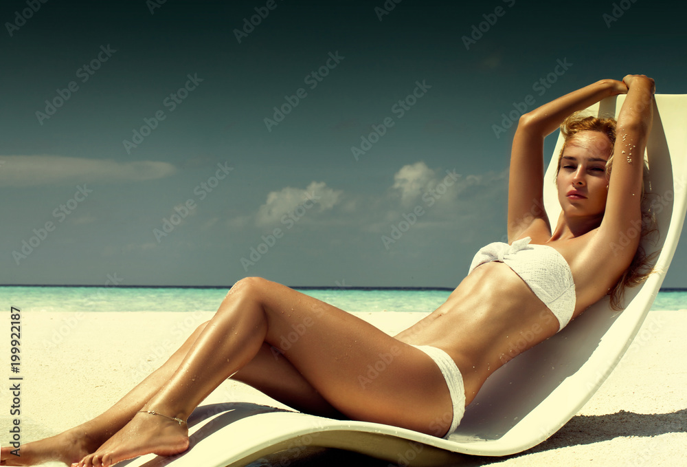 Fototapety, obrazy: Summer girl model with tanned sexy body. Posing in the white chair on the beach of the tropical island