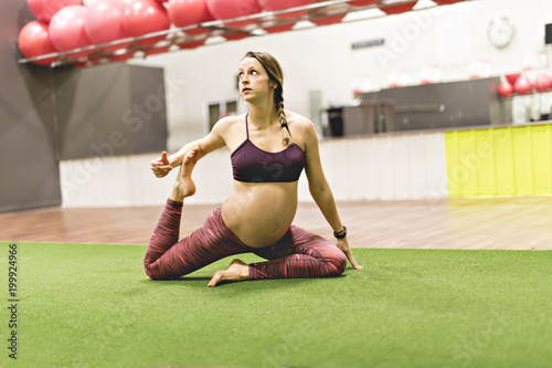 Pregnant woman is doing exercises at the gym Wallpaper Mural
