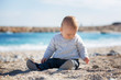 Little baby boy, playing on the beach with sand and pebbles on a sunny day