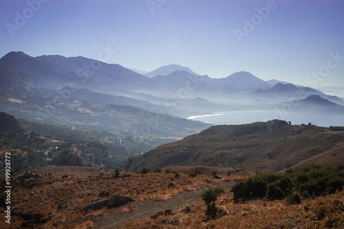 Staande foto Chocoladebruin Seascape and mountains in fog on island of Crete
