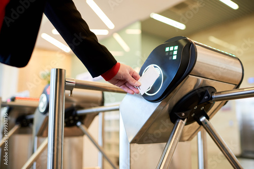 Fotografie, Obraz  Close up of unrecognizable businesswoman swiping card passing turnstile to enter