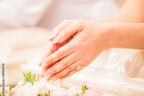 Aluminium Prints Manicure Hands pouring blessing water into bride's bands, Thai wedding.