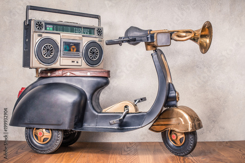 Poster Scooter Retro radio with cassette tape recorder on old black toy scooter from circa 80s in front concrete textured wall background. Listening music concept. Vintage style filtered photo