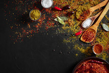 Assorted Spices On Dark Black Background. Seasonings For Food. Curry, Paprika, Pepper, Cardamom, Turmeric. Top View.
